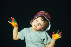 A fun little artist covered in paint. Boy with smeared hands in paint on a dark background . Cheerful artist royalty free stock photos
