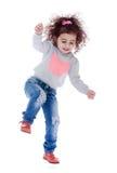 Fun little curly girl fun jumps Royalty Free Stock Image