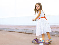 Fun little girl in dress on the scooter in the city Stock Photography