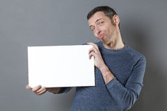 Fun looking man questioning what he displays on his copy space banner Stock Photography