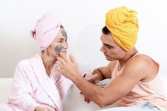 Fun loving couple cares for the skin. Sitting on the couch in towels and cause each other clay mask on the face. Health care, beau Stock Photo