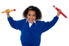 Fun loving elementary girl dancing with pencils Stock Photography