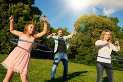 Fun loving family playing with hula hoops together outside stock images