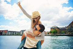 Fun loving young couple frolicking at a waterfront. Fun loving young couple frolicking at the waterfront of a historic town riding piggy back and laughing Stock Images