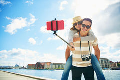 Fun loving young tourists taking a selfie. With their mobile phone on a stick grinningas they pose with the young women taking a piggy back ride on the man Royalty Free Stock Photo
