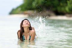 Fun loving young woman splashing Royalty Free Stock Image