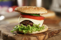 Fun made fresh burger with marble beef, cheese and vegetables on olive board Royalty Free Stock Photo