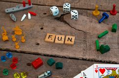 `Fun` made from Scrabble game letters. Risk, Battleship pieces, Monopoly, Settler of Catan and other game pieces royalty free stock photos