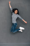 Fun in midair. Beautiful young cheerful Asian woman looking at camera with smile while jumping against grey background Royalty Free Stock Image