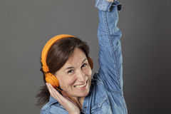Fun middle aged woman listening to music with arms raised Royalty Free Stock Photo