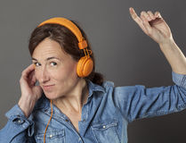 Fun middle aged woman listening to music for joyous wellbeing Royalty Free Stock Photos