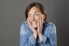 Fun middle aged woman winking for cheerful flirting, humorous portrait. Fun middle aged woman winking with sexy hands touching her face for cheerful flirting Stock Photo