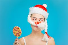 Fun miss santa with candy. And fake moustache on blue background stock photo