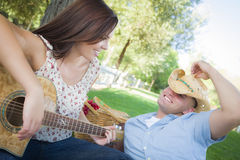 Fun Mixed Race Couple with Guitar and Cowboy Hat in Park Stock Photo