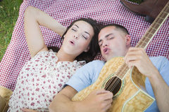 Fun Mixed Race Couple at the Park Playing Guitar and Singing Royalty Free Stock Photo