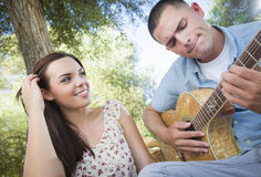 Fun Mixed Race Couple Playing Guitar and Singing Outdoors Royalty Free Stock Photo