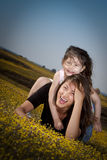 Fun with mom. Little girl on her moms back laughing and having fun Stock Photos