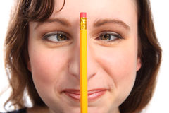 Fun moment as girl holds pencil between her eyes Stock Photos