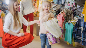 Fun mother-daughter time in the children`s clothing store. Children`s clothing store - a young mother and a little girl choose clothes and have fun Royalty Free Stock Photos