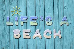 Life`s A Beach Motivational Quote. The fun, motivational quote or phrasing, Life`s A Beach written on blue, old, grungy wood planks royalty free stock photo