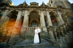 Fun newly married couple embrace near the Church Royalty Free Stock Image