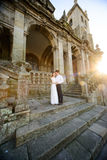 Fun newly married couple embrace near the Church Royalty Free Stock Photos