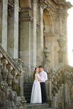 Fun newly married couple embrace near the Church Stock Photo
