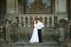 Fun newly married couple embrace near the Church Royalty Free Stock Photo