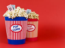 Fun night for four. Two popcorn buckets over a red background. Movie stubs sitting over the popcorn Stock Photo