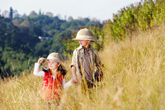 Fun outdoor children playing. Children brother and sister playing outdoors pretending to be on safari and having fun together with binoculars and hats stock photos