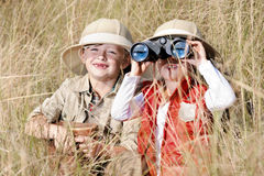 Fun outdoor children playing. Children brother and sister playing outdoors pretending to be on safari and having fun together with binoculars and hats stock images