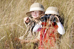 Fun outdoor children playing. Children brother and sister playing outdoors pretending to be on safari and having fun together with binoculars and hats royalty free stock photos