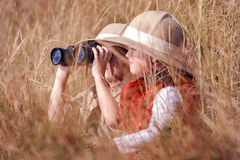 Fun outdoor children playing. Children brother and sister playing outdoors pretending to be on safari and having fun together with binoculars and hats stock photo