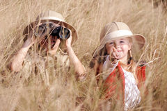 Fun outdoor children playing. Children brother and sister playing outdoors pretending to be on safari and having fun together with binoculars and hats royalty free stock images