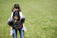 Fun in the park. Teenage girl carrying sister by piggyback in park Royalty Free Stock Photo