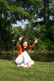 Fun in the park. A young woman sits in a park next to a pond, smiling widely as she poses with her fingers forming the peace/victory sign Stock Image
