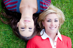Fun In Park. Two young attractive women lying together on the grass Royalty Free Stock Images