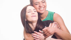 Fun pastime of two girlfriends. Two best friends hugging and smiling happily at the camera. Brunette and a mulatto girl. isolated on gray background stock video footage