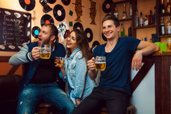 Fun people at bar looking away drinking and laughs. Horizontal photo Royalty Free Stock Photography