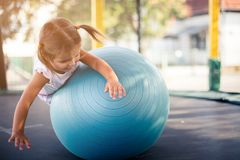 Fun on Pilates ball. Little girl playing and using Pilates ball. Copy space stock images