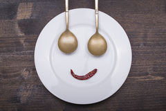 Fun plate - facial image on the plate with spoons and pepper Royalty Free Stock Photo