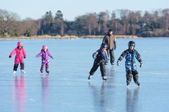 Fun play on ice. Listerby, Sweden - January 17, 2016: Children and adult are having some fun on the frozen sea ice. Ice is smooth and the landscape is visible in Stock Image
