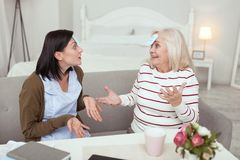 Joyful elder woman and caregiver guessing character Stock Photo