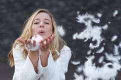 Fun playful young woman blowing white feathers Stock Photos