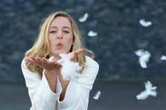 Fun playful young woman blowing white feathers Royalty Free Stock Images