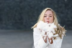 Fun playful young woman blowing white feathers Stock Photo