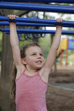 Fun At the Playground - Little Girl Plays on Monkey Bars Royalty Free Stock Images