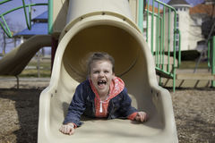 Fun at the Playground - Little Girl Slides Down Slide Royalty Free Stock Images