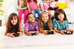 Fun playing video games. Close portrait of a group of diversity looking kids, boys and girls playing videogame, laying on the floor in kids room Royalty Free Stock Image