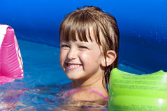Fun in the pool. A little girl taking fun in a swimming pool water Royalty Free Stock Images